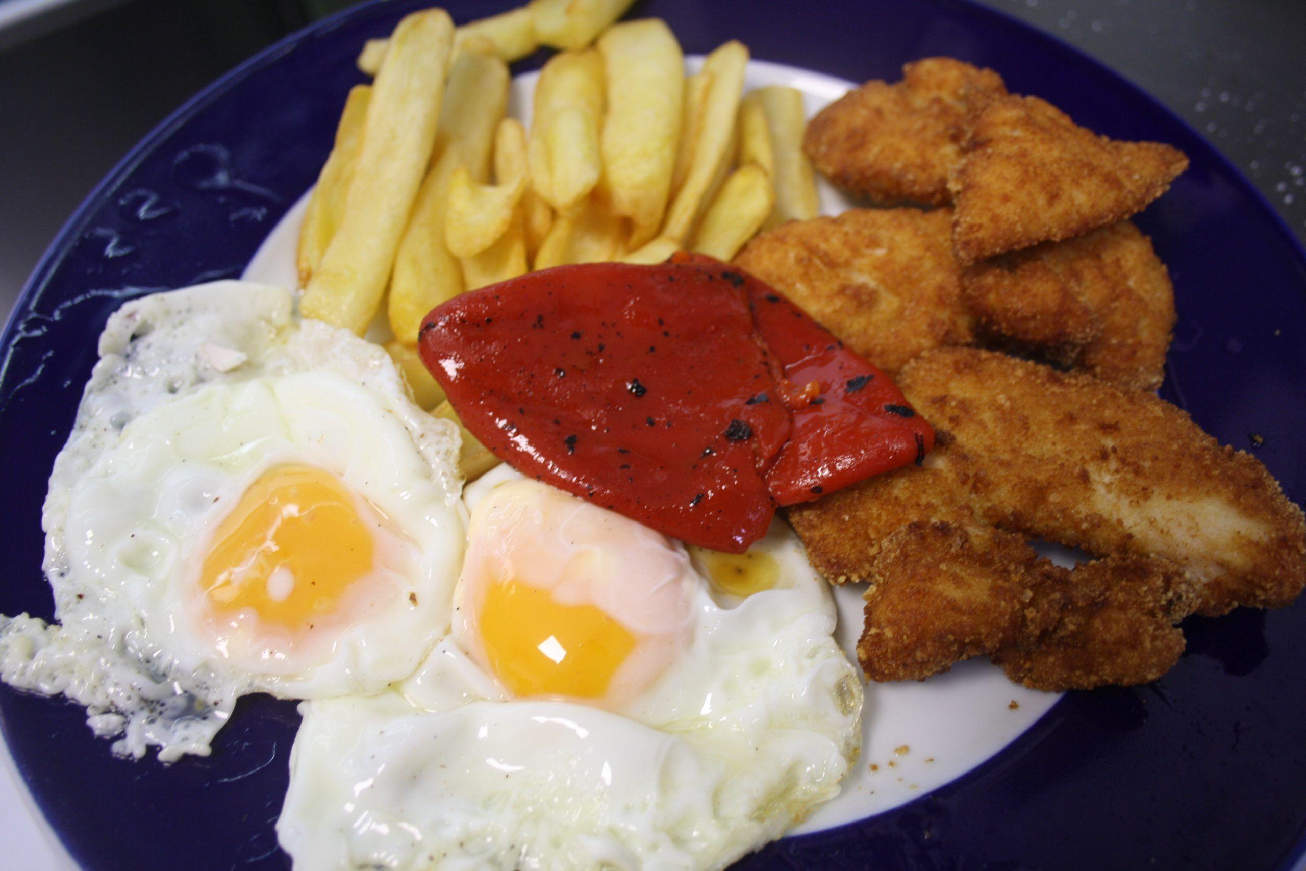 Tiras de pollo empanadas, huevos, piquillos y patatas