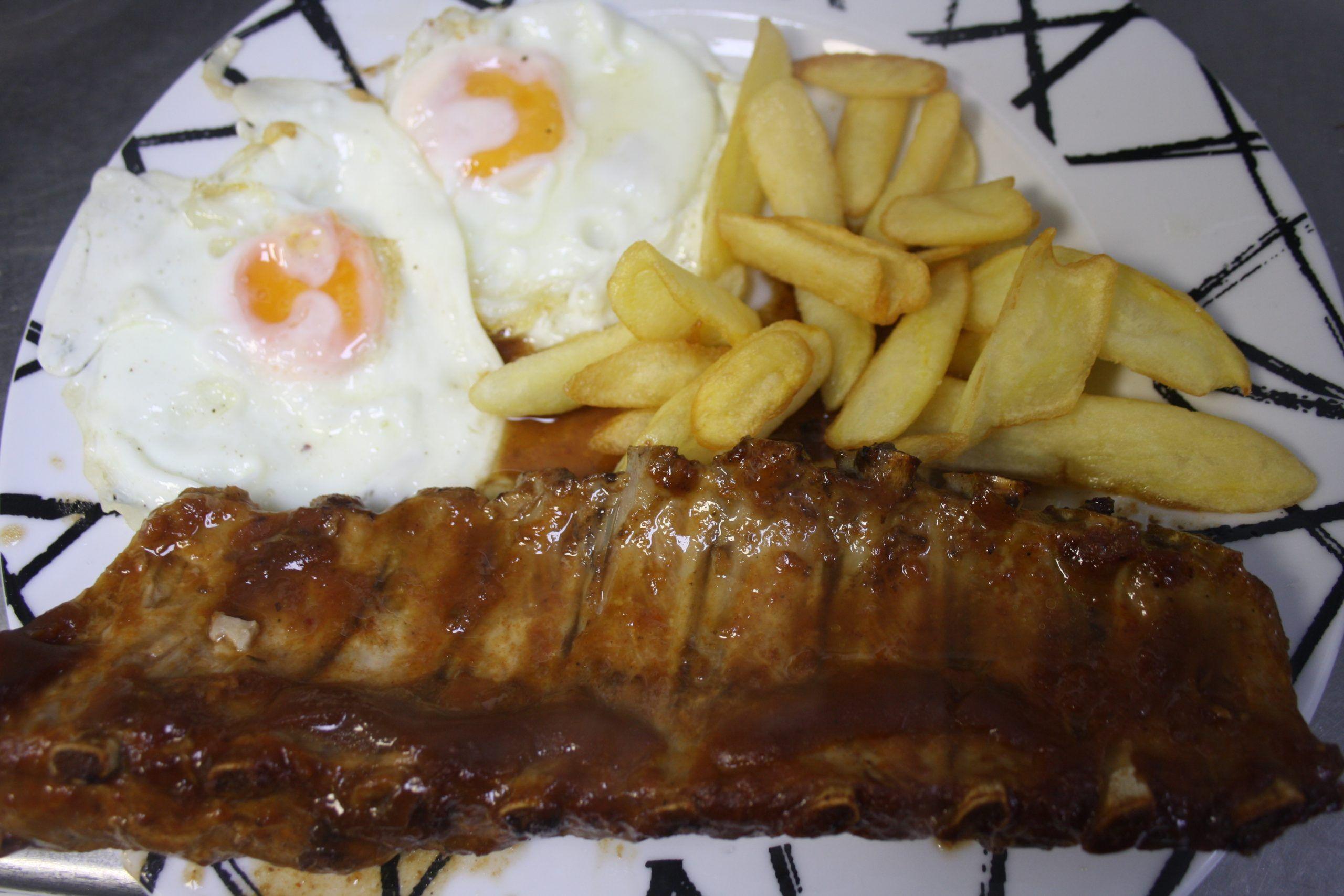 Costillar de cerdo asado con huevos fritos y patatas